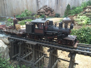Climax #6 powers upgrade with the log skidder and empty log cars as it passes over the Priya Canyon Trestle.